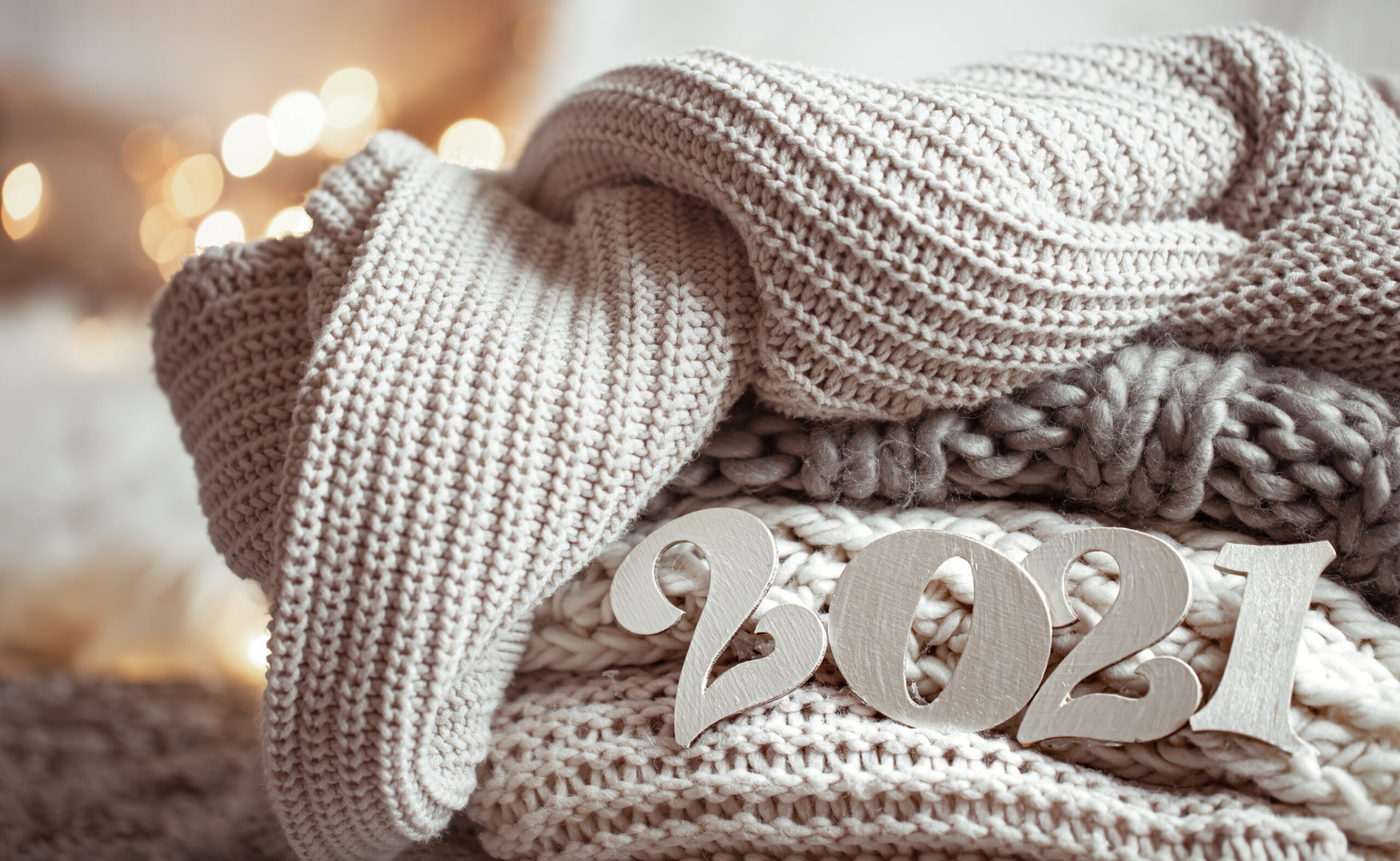 Cozy new year composition with knitted pastel colored wooden numbers 2021 close up.